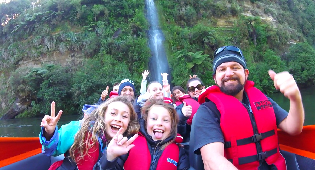 Camjet jet boat with a family on board doing a pose in front of a big waterfall. Jet boat New Zealand.