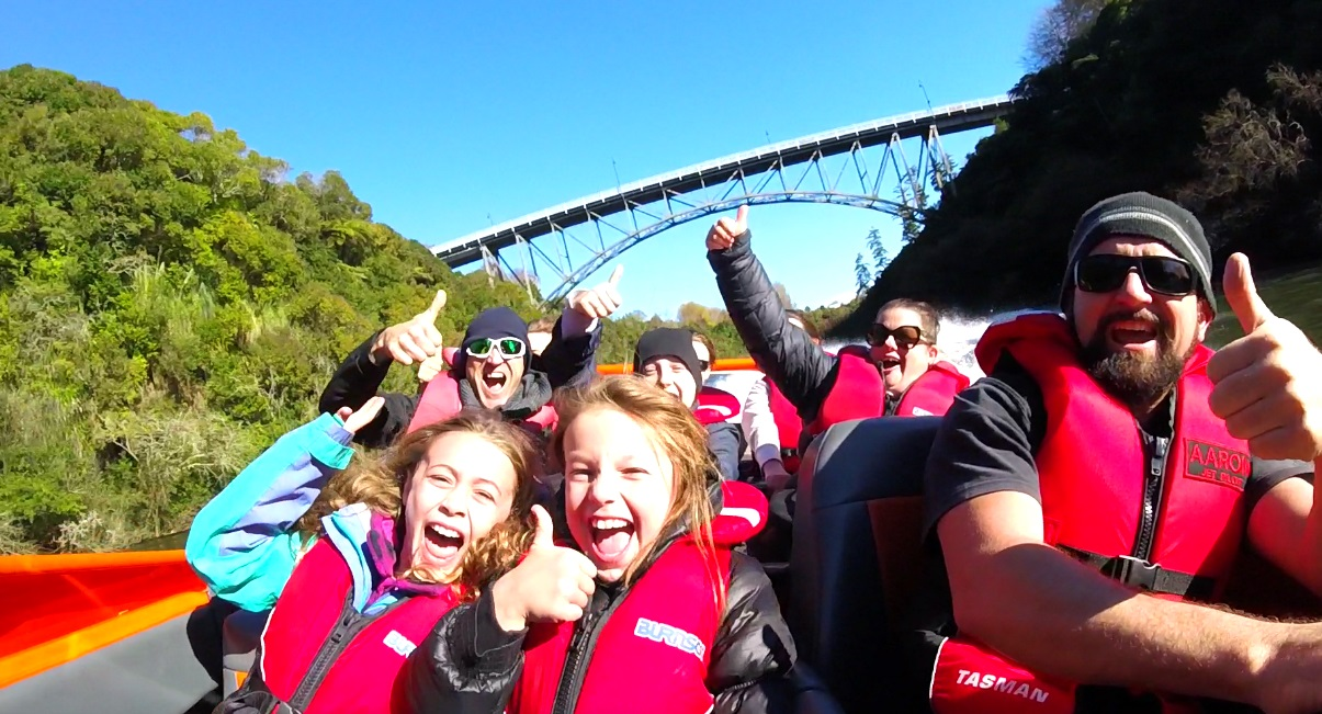 Camjet jet boat in New Zealand with a family on boat with a large bridge in the background.